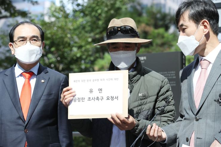 Lee Rae-jin, center, the elder brother of the South Korean official who was shot dead by North Korean troops after floating into the North's territorial waters late last month, holds a letter requesting the United Nations investigate the case, before delivering it to the United Nations Human Rights Office in Seoul, Tuesday. Rep. Ha Tae-keung, right, and Rep. Tae Yong-ho of the main opposition People Power Party accompanied Lee. Yonhap