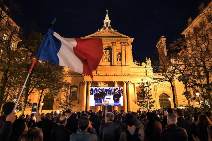 An attendee waves a French flag as people gather on the Place de la Sorbonne in Paris on Oct. 21 (local time), to watch a live broadcast on a giant screen of a national homage at the Sorbonne University to French teacher Samuel Paty, who was beheaded for showing cartoons of the Prophet Mohamed in his civics class. AFP-Yonhap