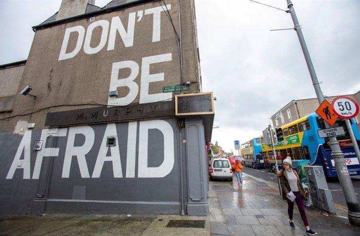 A pedestrian walks past a mural reading 'Don't Be Afraid' in Dublin on Oct. 19, 2020. AFP