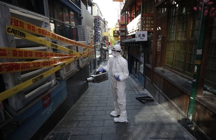 A health official wearing protective gear disinfects property in Seoul, Thursday, as a precaution against the spread of COVID-19. AP