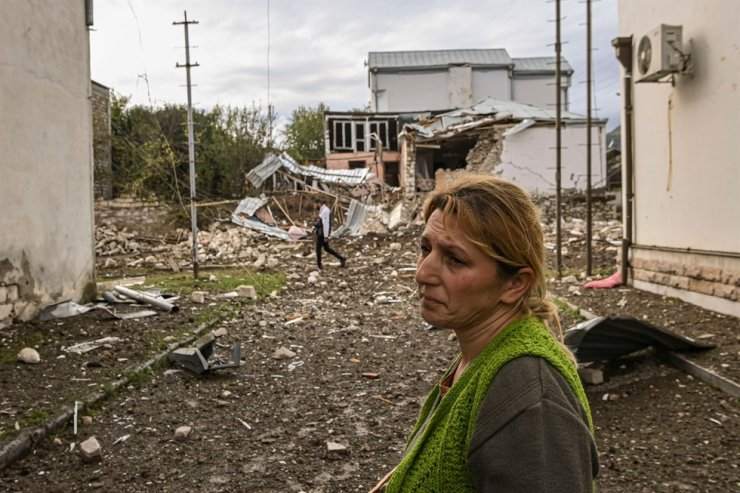 A woman stands in front of a destroyed house after a late October 7th sheling in the breakaway Nagorno-Karabakh region's main city of Stepanakert on Oct. 8, 2020, during the ongoing fighting between Armenia and Azerbaijan. AFP