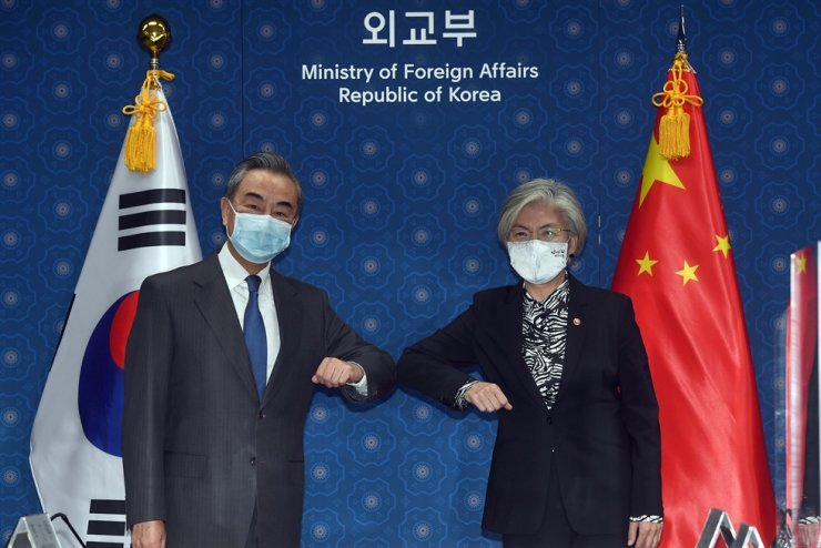 Foreign Minister Kang Kyung-wha, right, bumps elbows with her Chinese counterpart Wang Yi before their talks at the ministry office in Seoul, Thursday. Yonhap