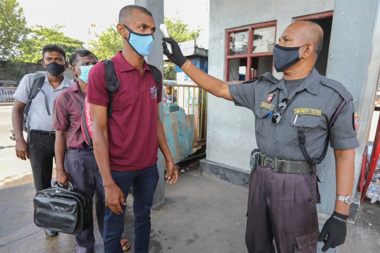 A Security officer check the body temperature of passengers at a bus terminal amid the coronavirus pandemic in Colombo, Sri Lanka, Nov. 9. EPA-Yonhap