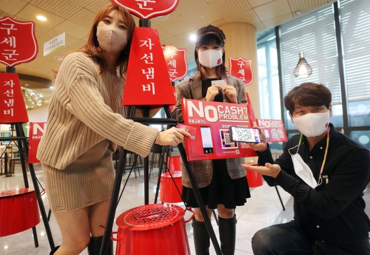 Honorary ambassadors for the Salvation Army introduce a 'digital kettle' that is equipped with smart chips and QR codes to allow people to easily donate through mobile payment systems, at the organization's headquarters in Seoul, Thursday. Yonhap