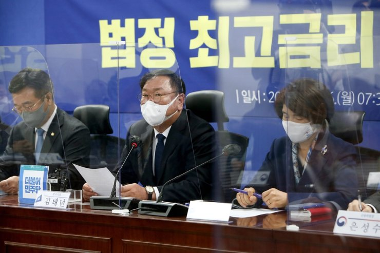 Democratic Party of Korea floor leader Kim Tae-nyeon, center, speaks during a meeting with government officials at the National Assembly on lowering the maximum interest rate, Monday. / Yonhap