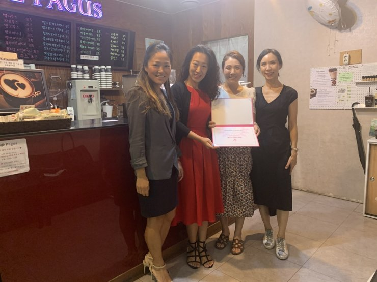A donation ceremony between SIWA and KUMFA at Cafe Pagus in Seoul. From left to right, SIWA member Eunice Go, SIWA President Veronica Koon, KUMFA President Megy Kim and SIWA committee welfare chair Han Sung-hwa. / Courtesy of SIWA