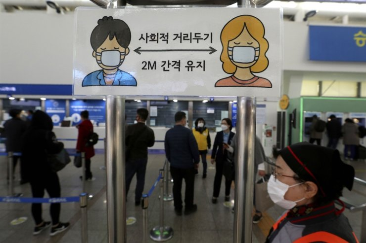 A social distancing sign is seen as people wait to buy tickets at the Seoul Railway Station in Seoul, Friday, Nov. 13, 2020. AP