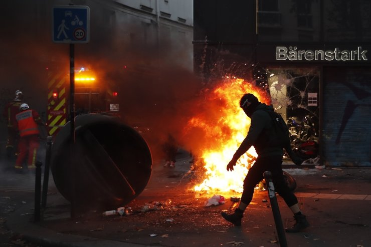 A protester walks past a fire set up by protesters during a demonstration against a security law that would restrict sharing images of police, Saturday, Nov. 28, 2020, in Paris. AP