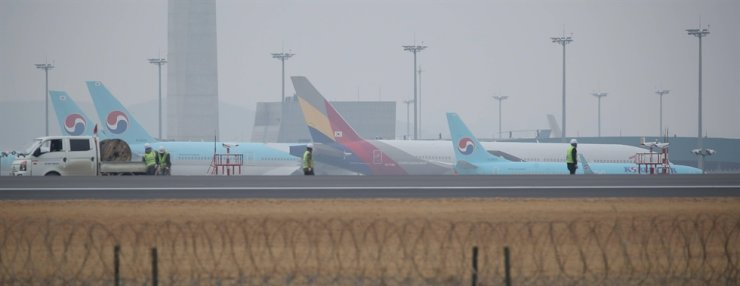 Passenger planes of the country's top flag carrier Korean Air and No. 2 carrier Asiana Airlines are parked at Incheon International Airport, Tuesday, a day after Korean Air announced a decision to take over its smaller local rival. / Yonhap