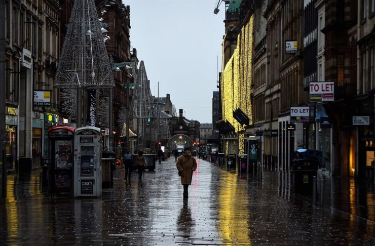 Pedestrians walk along a near-deserted Buchanan Street in central Glasgow, Nov. 24, 2020, during further coronavirus restrictions in the city. AFP