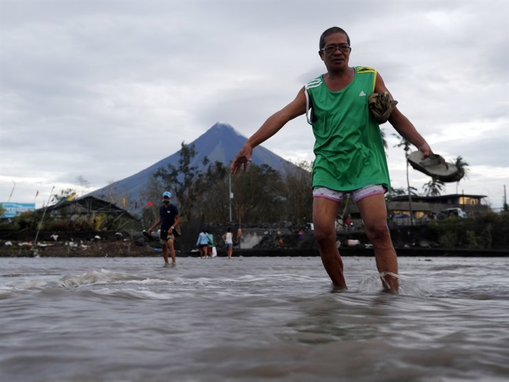 Villagers wade on flood water brought by a lahar flow due to typhoon Goni at the foot of Mayon volcano in Legaspi city, Albay province, Philippines, Nov. 3, 2020. EPA