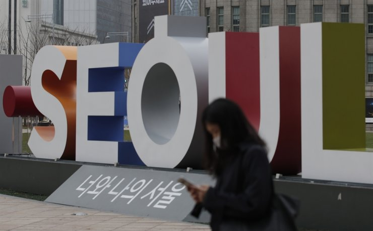 A woman wearing a face mask walks near the display of South Korea's capital Seoul logo in Seoul, Wednesday, Nov. 18, 2020. AP
