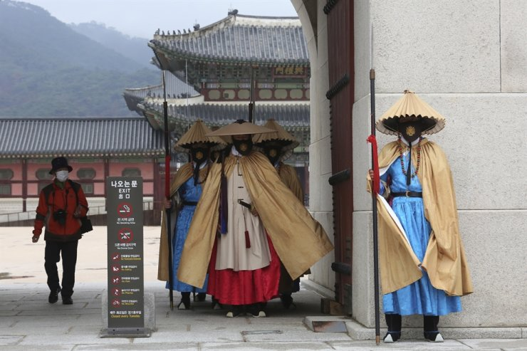 Imperial guards wearing face masks stand outside the Gyeongbok Palace in Seoul, Thursday, Nov. 19, 2020. AP