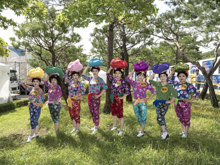 Eight middle-aged women, who performed as a team for the 2019 National Song Contest held in Seoul, pose with their colorful stage costumes. / Courtesy of Byun Soon-choel