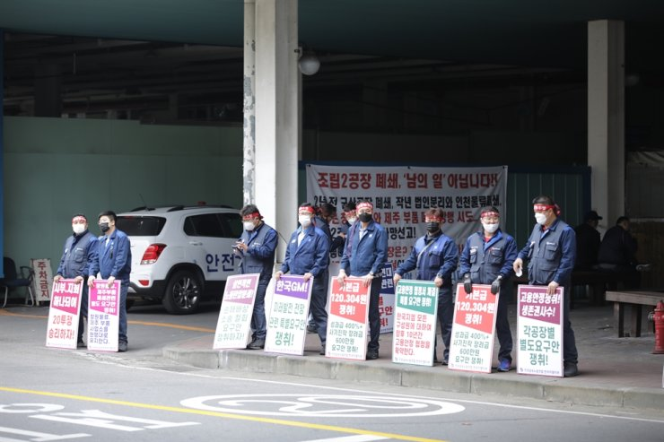 Members of the GM Korea workers' union hold banners during a protest at the company's Incheon plant, Tuesday. Courtesy of GM Korea union