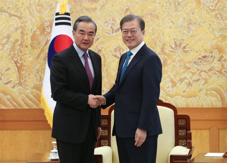 President Moon Jae-in, right, shakes hands with Chinese foreign minister Wang Yi on Dec. 5, 2019 at Cheong Wa Dae. Korea Times file