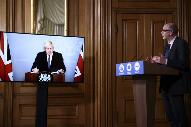 Britain's Prime Minister Boris Johnson appears on screen during a coronavirus news conference with Director of the Oxford Vaccine Group Andrew Pollard, right, giving an update about COVID-19 pandemic, at Downing Street in London, Monday Nov. 23, 2020. AP