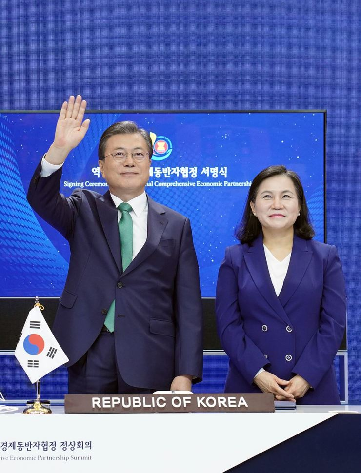 President Moon Jae-in, left, and Trade Minister Yoo Myung-hee take part in a virtual signing ceremony of the RCEP, the world's largest FTA, on Nov.15, at Cheong Wa Dae. Experts note that Korea is well positioned to serve as a catalyst for dialogue with its rising status as a middle power and an active player in multilateral trade and diplomacy. Courtesy of Cheong Wa Dae