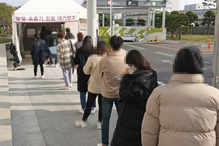 People queue up for COVID-19 tests at Korea University Anam Hospital in Seoul, Monday. Eight cases have been confirmed involving members of an ice hockey club of the university. Yonhap