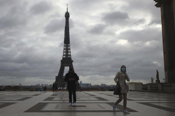 People wearing face masks walk near the Eiffel Tower in Paris, Thursday, Nov. 19, 2020. AP