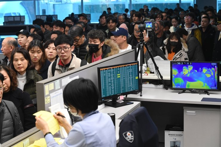 In this photo from January 2020, passengers departing for China go through a custom desk at the Incheon International Airport's Terminal 2 where an official checks their body temperatures and quarantine history reports. Korea Times file