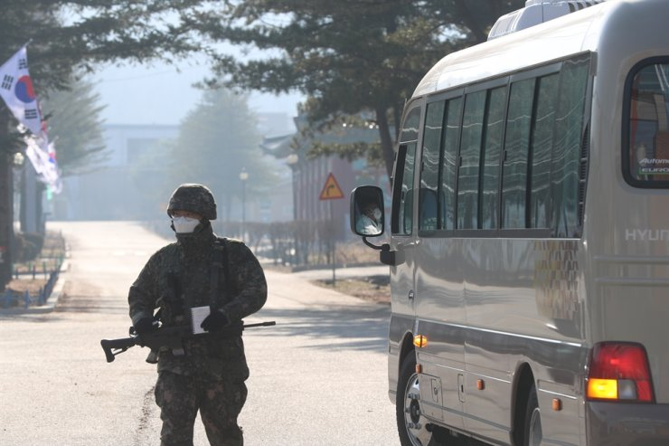 A bus to carry COVID-19 patients stands by in front of the boot camp of the Army's 5th Infantry Division in Yeoncheon, Gyeonggi Province, on Nov. 26 as nearly 70 infections were reported there. Yonhap