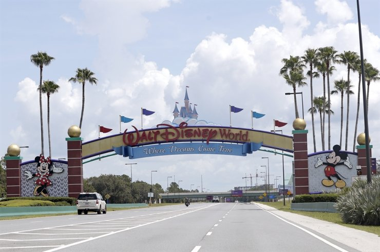 In this Thursday, July 2, 2020, file photo, cars drive under a sign greeting visitors near the entrance to Walt Disney World, in Lake Buena Vista, Fla. AP