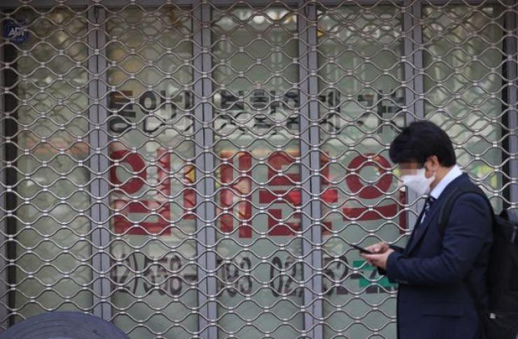 A man walks past a shuttered store in Seoul. Korea Times file