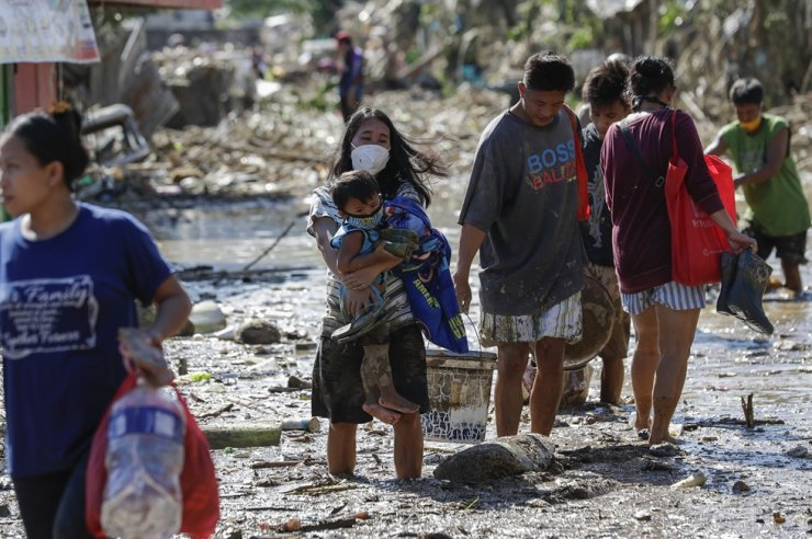 A woman carries her daughter through debris and floods in the typhoon-damaged Kasiglahan village in Rodriguez, Rizal province, Philippines, Friday, Nov. 13, 2020. AP