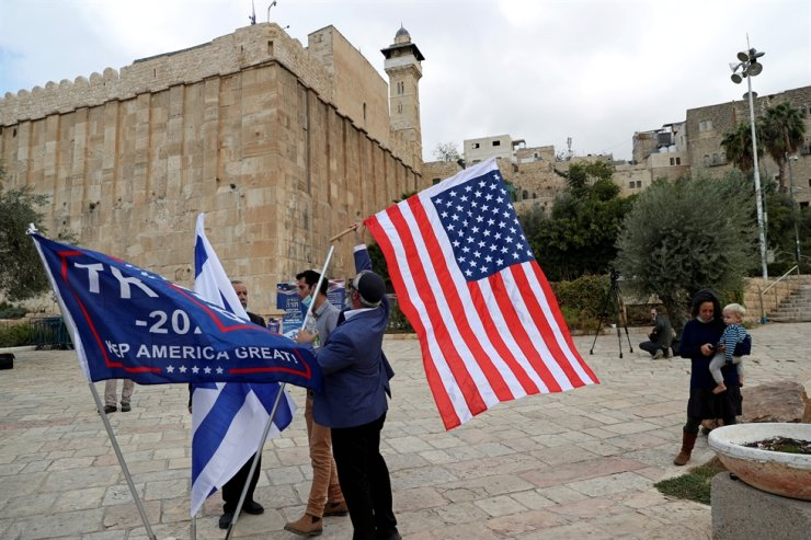 A man places a U.S. flag during a gathering to show support for U.S. President Donald Trump in the upcoming U.S. election, at the Cave of the Patriarchs, a site sacred to Jews and Muslims, in the Palestinian city of Hebron in the Israeli-occupied West Bank, Nov. 2, 2020. Reuters