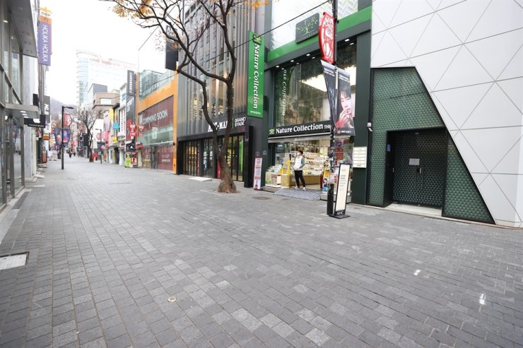 A street in Seoul's popular tourist district of Myeong-dong remains almost empty, Sunday, amid a surge in coronavirus cases in the country. Yonhap