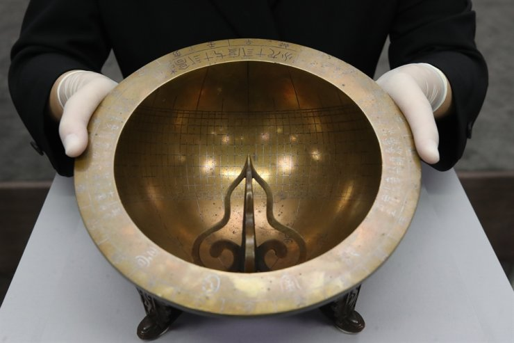 An official of the Cultural Heritage Administration holds 'Angbuilgu' metal sundial returned from the United States at the National Palace Museum of Korea, Tuesday. The sundial, estimated to be produced in the 18th century, is on public view through Dec. 20. Yonhap