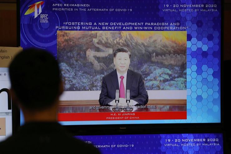 People look at a screen showing China's President Xi Jinping speaking during the virtual APEC CEO Dialogues 2020, at its command center in Kuala Lumpur, Malaysia November 19, 2020. /Reuters