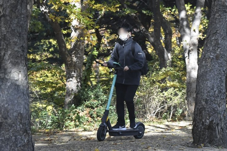 A man rides an electric scooter at Yonsei University in western Seoul on Tuesday. / Korea Times photo by Lee Han-ho