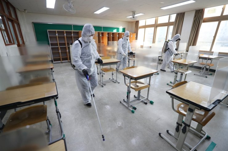 With South Korea's annual national college entrance exam slated on Dec. 3, the country's health inspectors on Nov. 26 disinfect a classroom in Daegu, one of the places where the exam will be held, to prevent spread of COVID-19. Yonhap