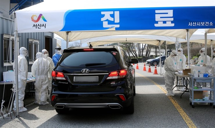 Officials at a Seosan public health center in South Chungcheong Province test visitors in a vehicle for COVID-19 on Nov. 13. The same day, eight members of Republic of Korea Air Force's 20th Fighter Wing stationed in the city tested positive with the virus. Courtesy of the Season public health center