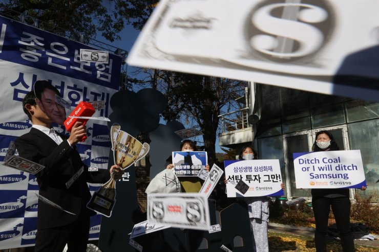 Members of the Korea Federation for Environmental Movements protest Samsung's insurance units' investments in coal-fired power plants, in front of the environmental group's headquarters in central Seoul, Tuesday. The group claimed Samsung's two insurers were responsible for the early deaths of over 30,000 people due to air pollution emitted by the power plants. / Yonhap