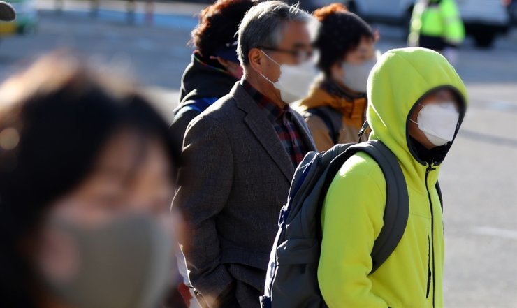 People bundled up against the cold weather wait for a traffic light to change in front of Dongnae Station in Busan, Wednesday. The Korea Meteorological Administration said temperatures nationwide dropped to near or below freezing Wednesday, noting that the strong autumn cold front causing the low temperatures would end Thursday afternoon. / Yonhap