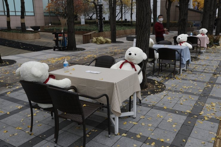 Tables and chairs are placed with hand sanitizers and stuffed toys while maintaining social distancing in Seoul, Wednesday, Nov. 18, 2020. AP