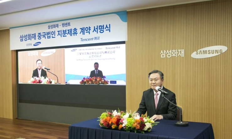 Samsung Fire & Marine Insurance CEO Choi Young-moo holds an online partnership ceremony with Ren Huichuan, an in-house adviser at Tencent, over their plan to establish a joint venture there, at the former's headquarters in Seoul on Thursday. Yonhap