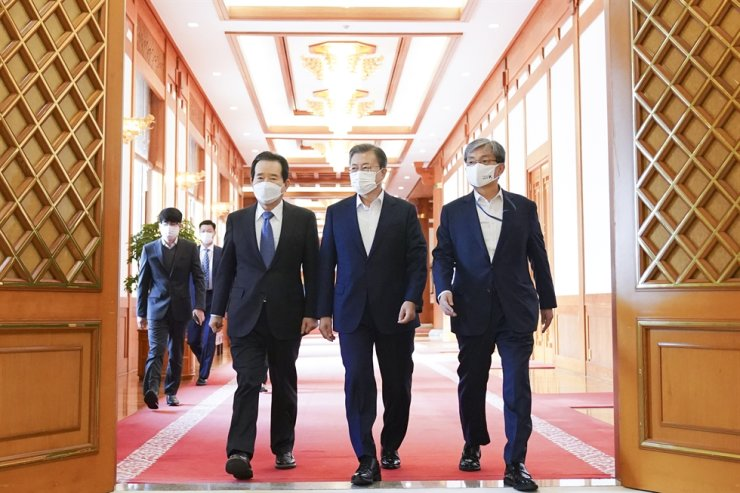 President Moon Jae-in, center, enters a special strategy meeting on low carbonization at Cheong Wa Dae, Friday, with Prime Minister Chung Sye-kyun, left, and presidential Chief of Staff Noh Young-min. On the same day, Cheong Wa Dae replaced Moon's secretary for foreign policy, the latest in a series of changes in key posts dealing with foreign affairs. Yonhap