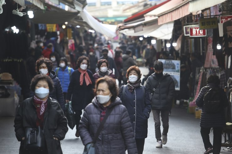 People wearing face masks walk through a market in Seoul, Friday, Nov. 27, 2020. AP