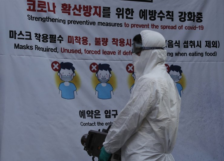 A health official from the district office wearing protective gear disinfects as a precaution against the coronavirus in Seoul, Thursday, Oct. 29, 2020. AP