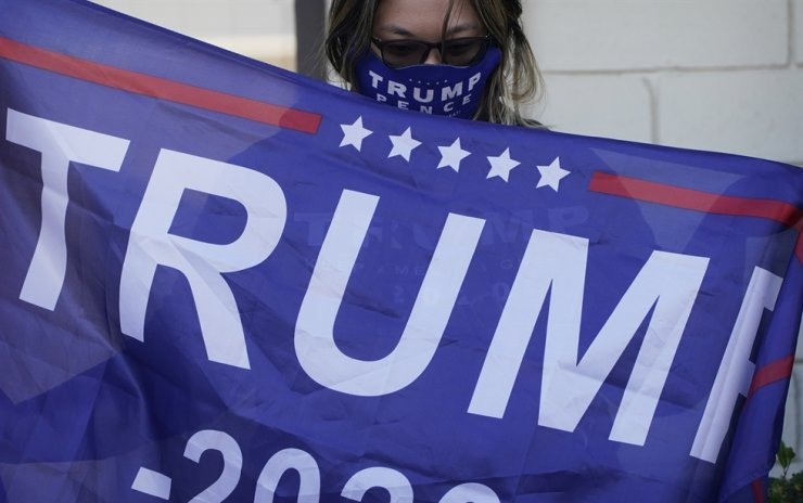 A supporter of U.S. President Donald Trump holds a flag during a news conference Tuesday, Nov. 17, 2020, in Las Vegas. AP