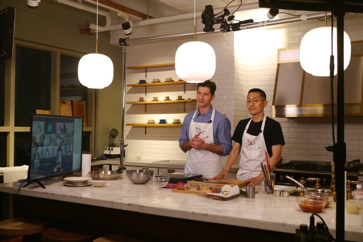 Chef Kang Min-goo, right, hosts a cooking class for hallyu fans abroad at a kitchen studio in Gangnam, Seoul, Saturday, with Italian TV personality Alberto Mondi helping him as a translator. Courtesy of Seoul Metropolitan Government