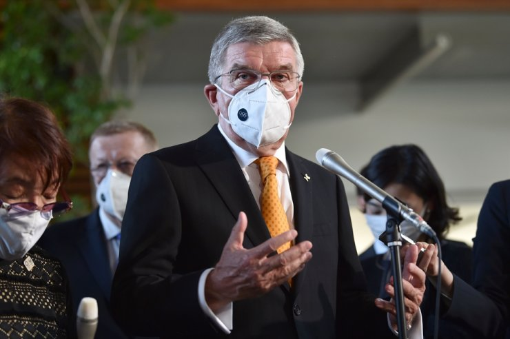 International Olympic Committee chief Thomas Bach wearing a face mask speaks to the media after his meeting with Japan's prime minister in Tokyo on Nov. 16, 2020. AFP