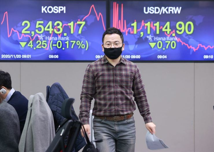 A dealer at Hana Bank walks in front of an electric board showing the decline of the benchmark KOSPI and the won-dollar exchange rate at the bank's head office in Seoul, Friday. Yonhap