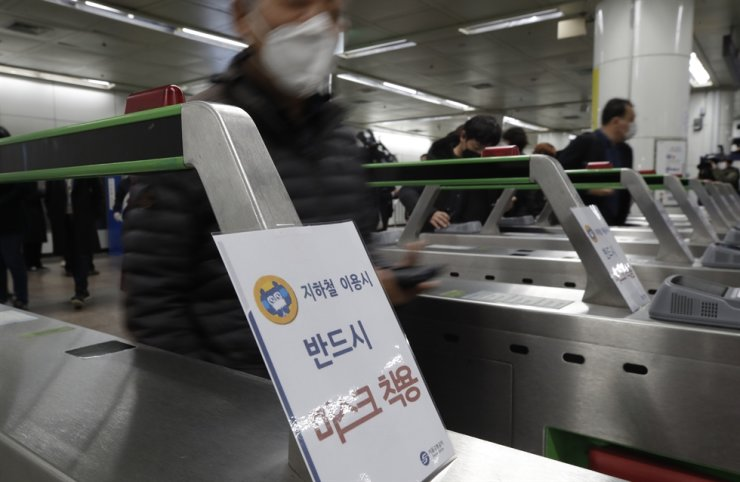 People wearing face masks walk past ticket gates at a subway station in Seoul, Friday, Nov. 13, 2020. AP
