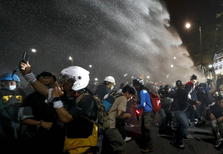 Police use water cannons to disperse pro-democracy protesters during a street march in Bangkok, Sunday, Nov. 8, 2020. AP