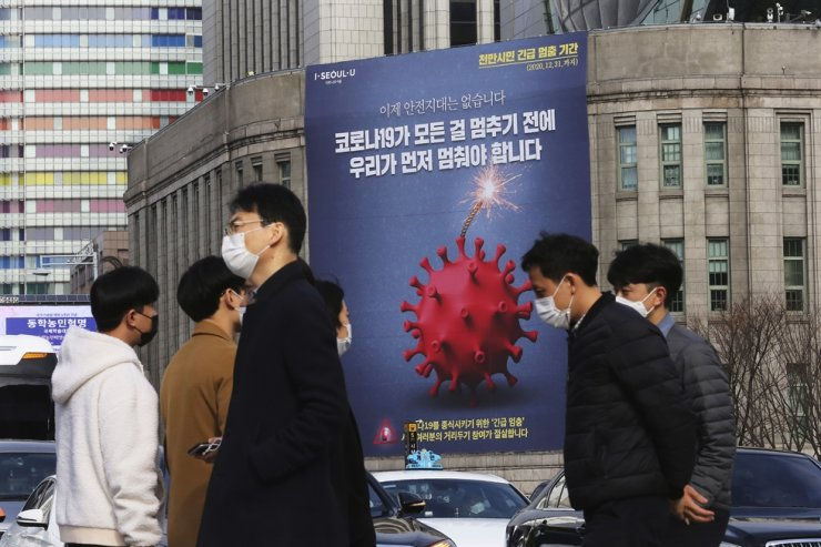 A banner emphasizing an enhanced social distancing campaign is displayed on the wall of Seoul City Hall in Seoul, Wednesday, Nov. 25, 2020. AP
